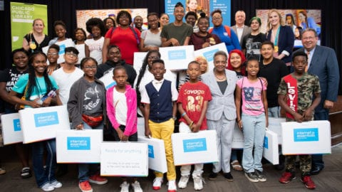 A group of children receive Internet Essentials laptops at an event in Chicago.